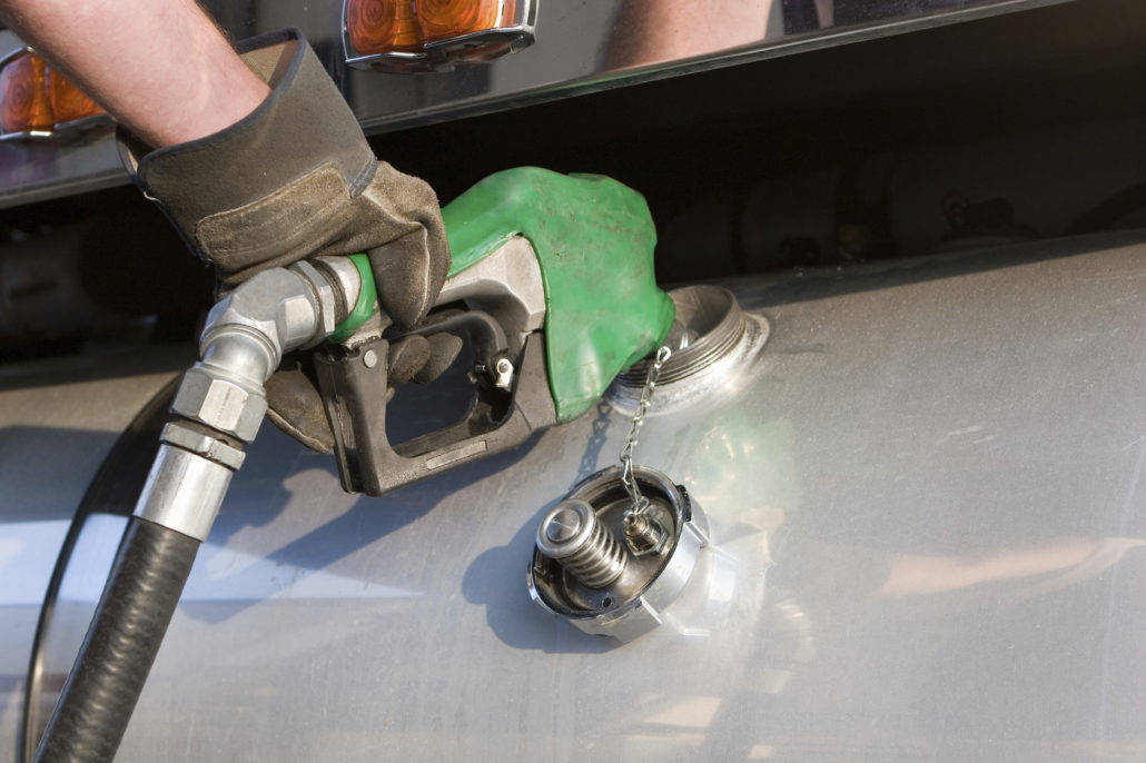A person filling a gas tank using a pump
